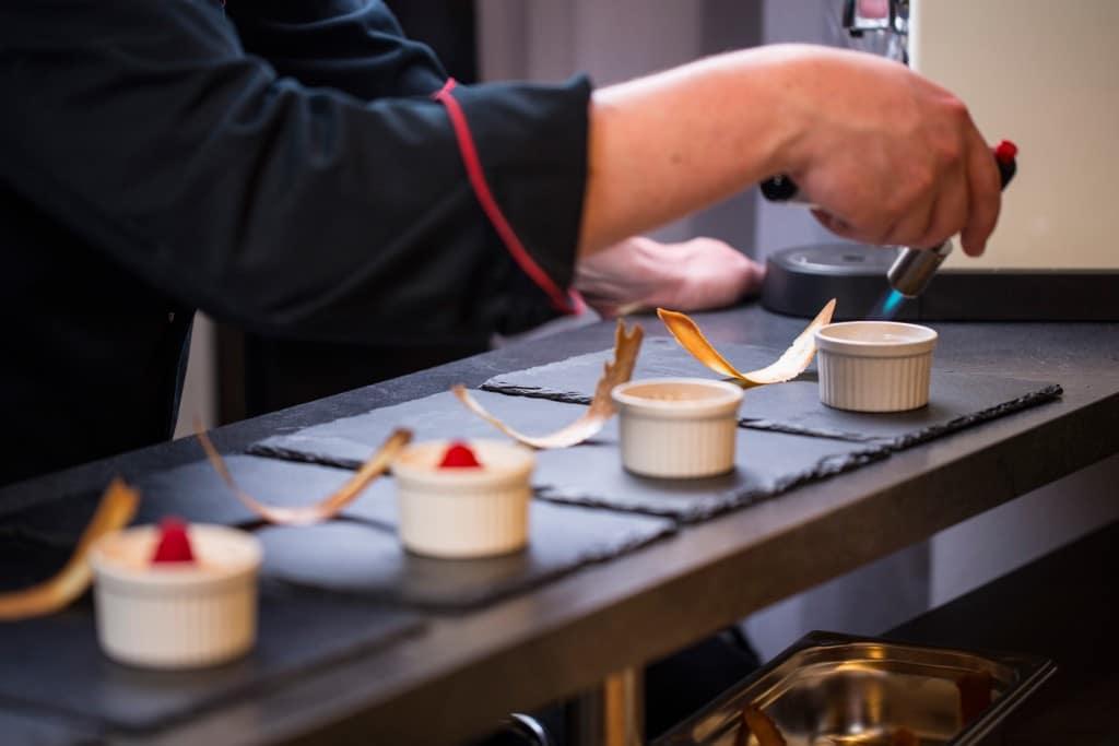Mitarbeiter von Kitchentalk Catering flambiert Nachspeise
